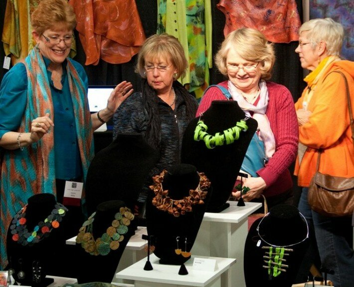 Collectors enjoy the wearable fiber of Joanna White and handmade jewelry by Nancy Raucch at the annual Carolina Artisan Craft Market in Raleigh, NC.